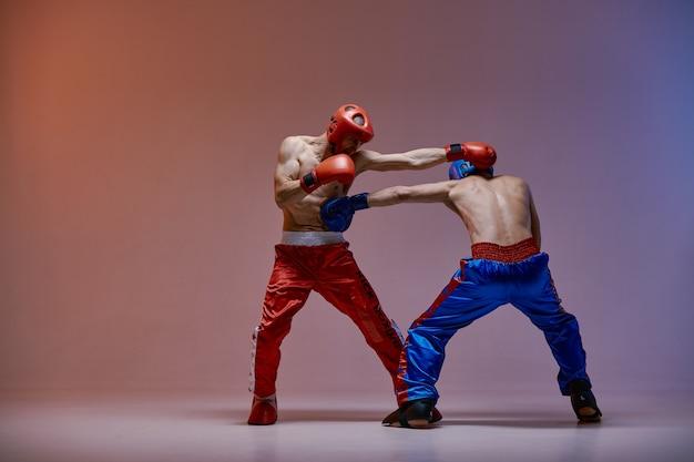 Jab de lutadores masculinos em luvas de boxe com torsos nus sob luz vermelha em estúdio, marcial