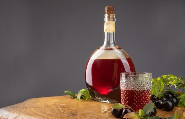 Jabuticaba, garrafa e copo de licor caseiro de jabuticaba na madeira
