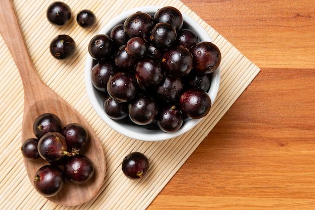 Jabuticaba na tigela e colher de pau - vista superior. jaboticaba ou jabuticaba é a uva brasileira nativa. espécie plinia cauliflora. berry brasileiro.
