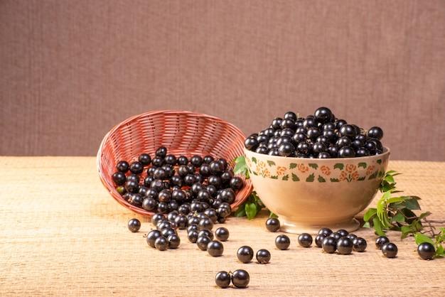 Jabuticabas recém colhidas em uma tigela e cestas dispostas em uma esteira de palha de foco seletivo