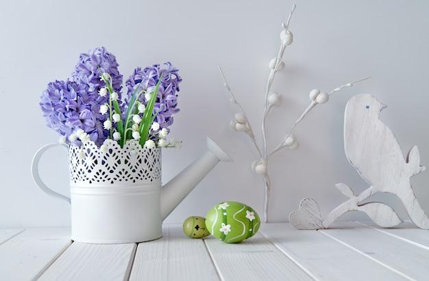 Jacinto azul e flores de lírio do vale, coração de madeira, pássaro e ovos de páscoa verdes