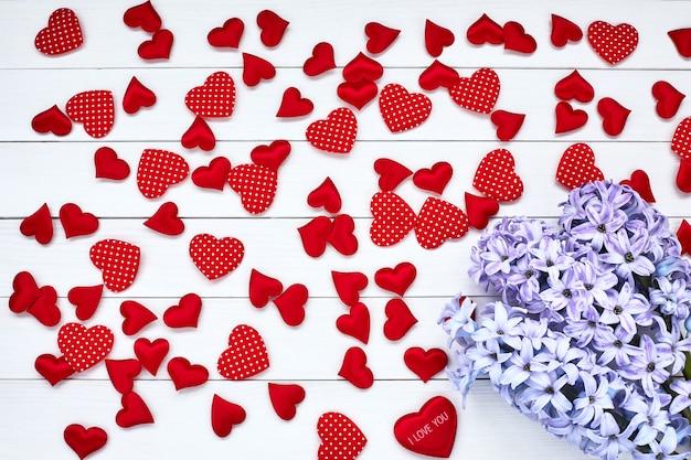 Jacinto roxo e corações vermelhos em fundo branco de madeira. plano de fundo dia dos namorados.