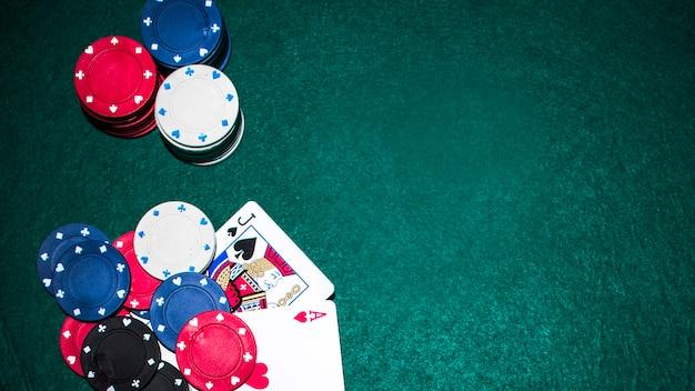 Jack de pá e coração ace cartão com fichas de casino na mesa de poker verde