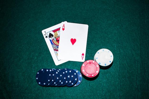 Jack de pá e coração ace cartão com pilha de fichas de casino na mesa de poker verde