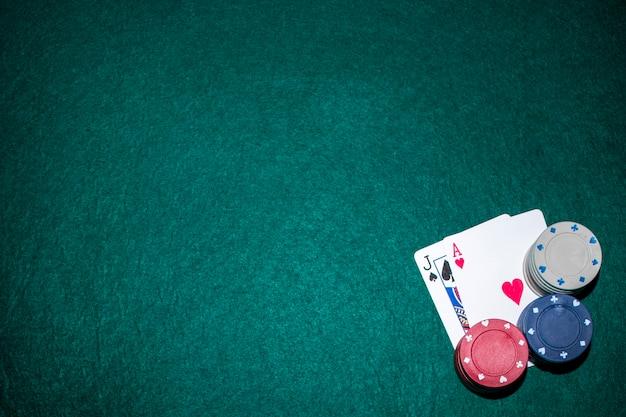 Jack de pá e coração ace cartão com pilha de fichas de cassino na mesa de poker verde