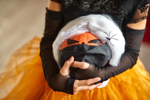 Jack o lantern, abóbora de halloween na máscara de proteção médica preta nas mãos da menina durante a celebração do halloween em casa covid19 coronavirus pandemia, copie o espaço.