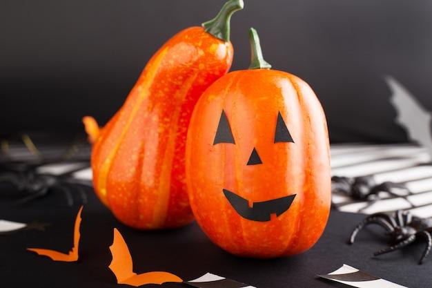 Jack-o'-lantern com aranha, morcegos de papel, fitas de abóbora, confetes em fundo preto com luzes. convite para festa de halloween, celebração. conceito de decoração de halloween