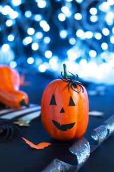 Jack-o'-lantern com aranha, morcegos de papel, fitas de abóbora, confetes em fundo preto com luzes. convite para festa de halloween, celebração. conceito de decorações de halloween.