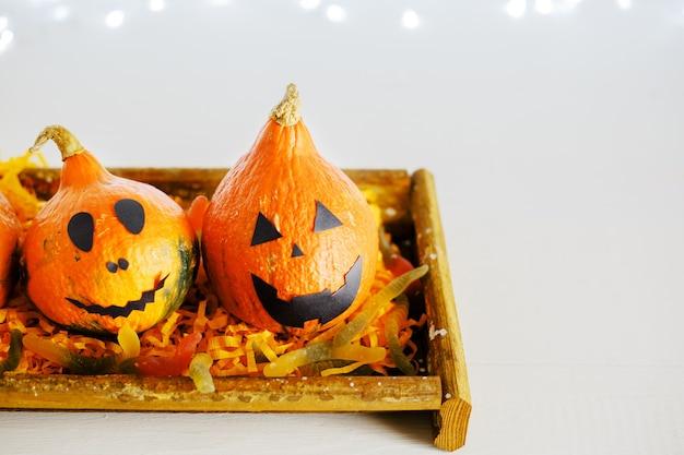 Jack-o'-lantern com doce doce, minhocas, aranhas em fundo branco com luzes. convite para festa de halloween feliz, celebração. conceito de decorações de halloween. copie o espaço.