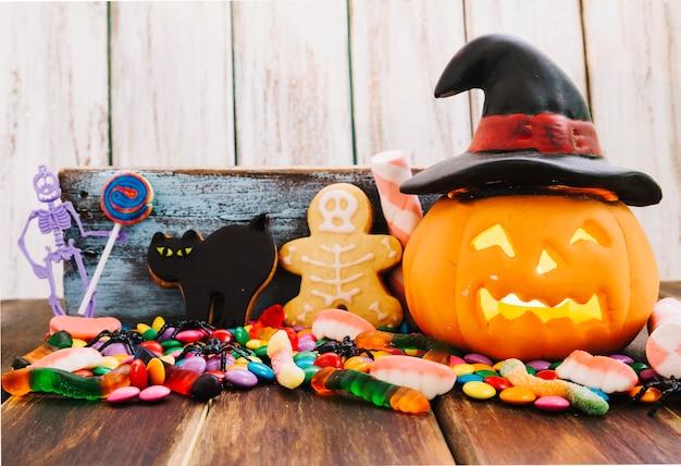 Jack-o-lantern em chapéu de bruxa e doces de halloween