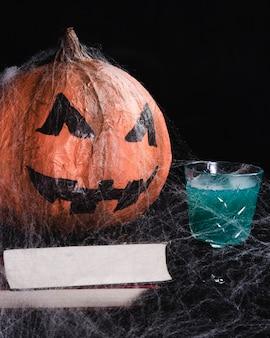 Jack-o'-lanterna com teia de aranha e bebida