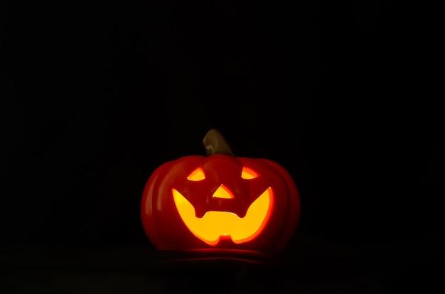 Jack-o-lanterna de halloween com luz amarela de uma vela em fundo escuro.
