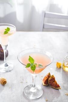 Jack rose cocktail com figos e mel na luz de fundo sobre o windows, plana leigos com espaço de cópia