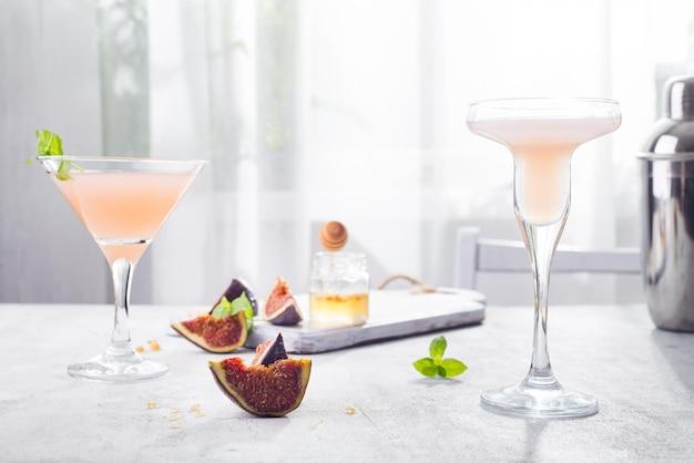 Jack rose cocktail com figos e mel no fundo claro sobre janelas