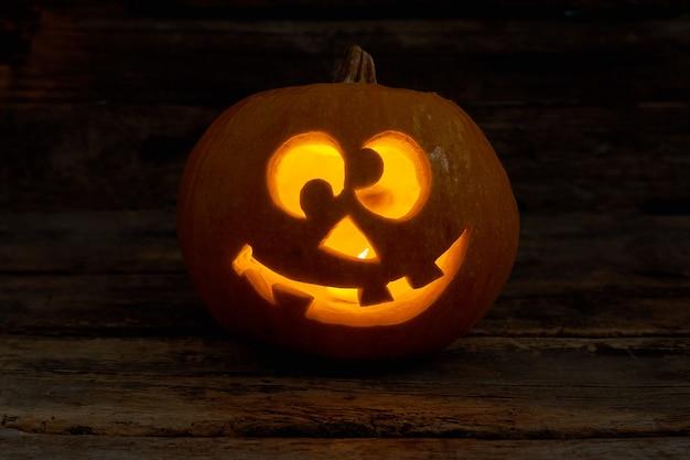 Jackolantern engraçado com vela brilhante cara de abóbora de halloween com vela acesa em fundo escuro ...