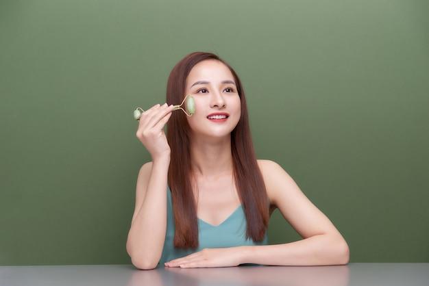 Jade roller. mulher de pijama de seda fazendo massagem facial. rotina matinal como parte da terapia anti-envelhecimento e anti-rugas