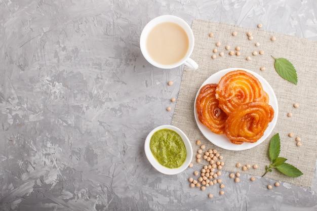 Jalebi indiano tradicional dos doces na placa branca com chutney da hortelã em um copyspace concreto cinzento. vista do topo.