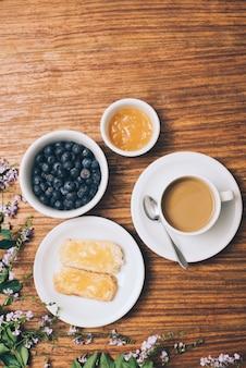Jam espalhado na torrada; amoras; xícara de café e flores cor de rosa na mesa de madeira