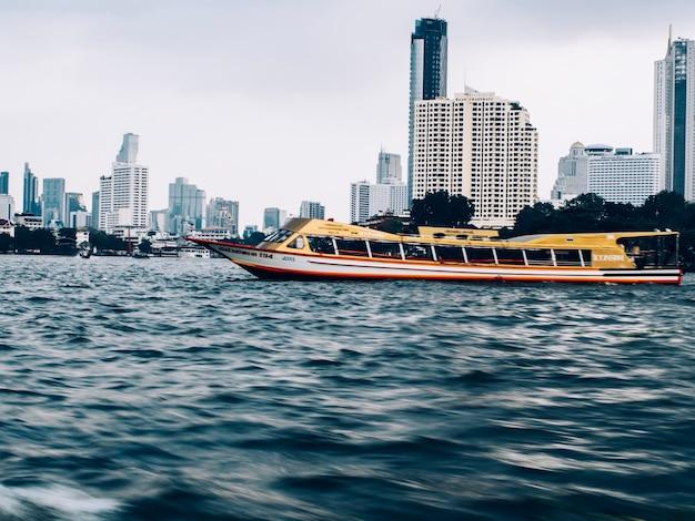 Janeiro de 2019, bangkok tailândia, rio de bangkok e edifício alto arranha-céu, paisagem urbana, barco-táxi serve para transporte público