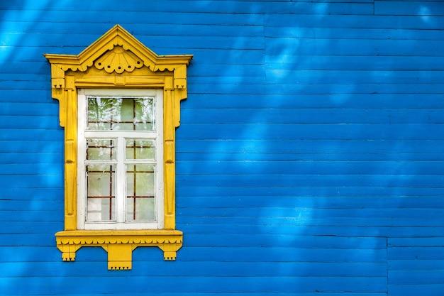 Janela amarela vintage em uma parede de madeira azul