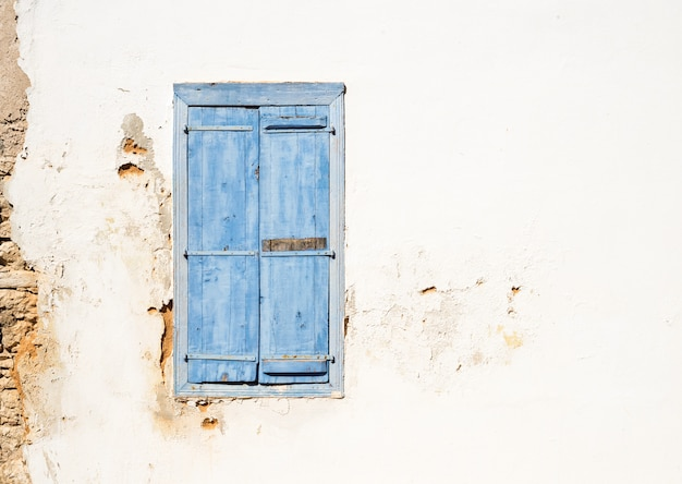 Janela antiga de estilo mediterrâneo. azul na parede clara com persianas fechadas.