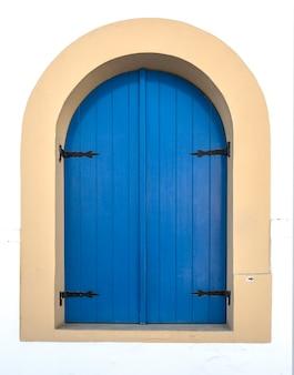 Janela azul na parede branca da velha casa