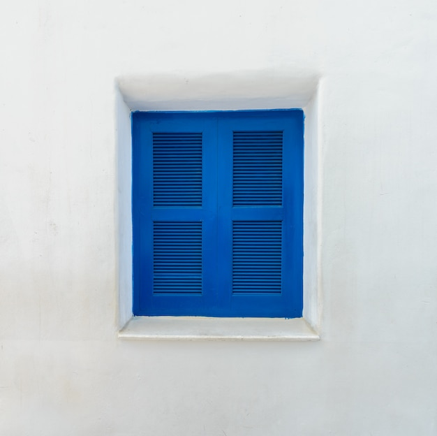 Janela azul na parede branca mediterrânea
