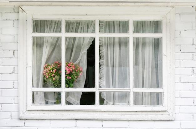 Janela branca com cortinas, um buquê de flores no parapeito da janela