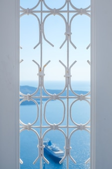 Janela branca e navio no céu azul e mar na ilha de santorini, oia, grécia