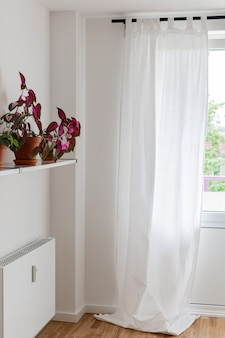 Janela com cortinas brancas e uma prateleira com flores e radiador
