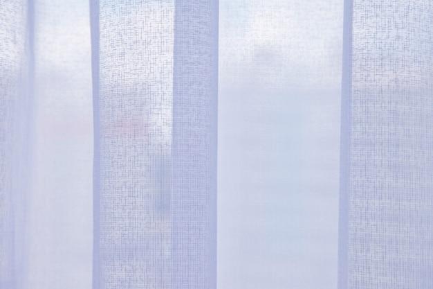 Janela com cortinas claras de tule, cidade do lado de fora