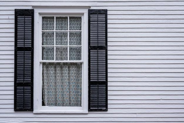 Janela com persianas abertas de uma casa de madeira de cor clara