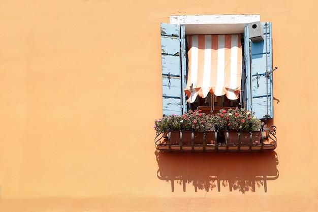 Janela com persianas de madeira azuis e toldo listrado em uma parede pintada de laranja