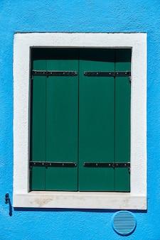 Janela com veneziana verde fechada na parede azul. itália, veneza, ilha de burano.