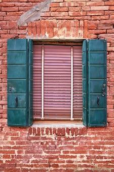 Janela com venezianas verdes na parede de tijolo vermelho das casas. itália, veneza, burano.