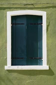 Janela com venezianas verdes na parede verde das casas. itália, veneza, burano.