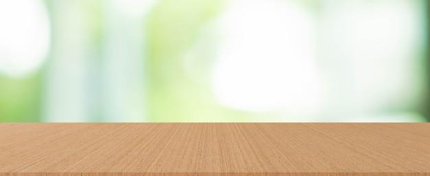 Janela da sala de estar com vista turva do jardim e fundo do balcão da mesa de madeira