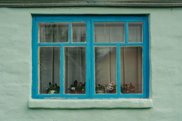 Janela de madeira azul de uma casa rústica verde velha com parede emplastrada.