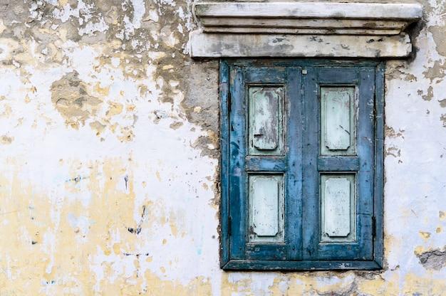 Janela de madeira azul velha com muro de concreto