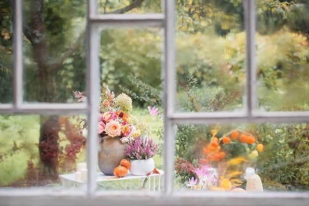 Janela de madeira branca velha com gotas de chuva e decoração de outono no jardim