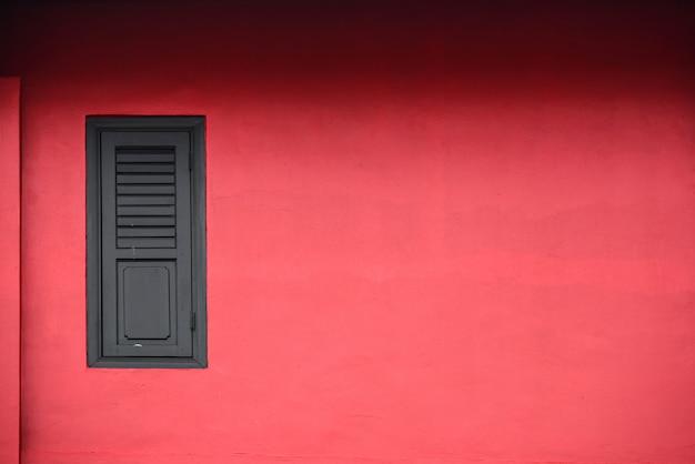 Janela de madeira na parede vermelha