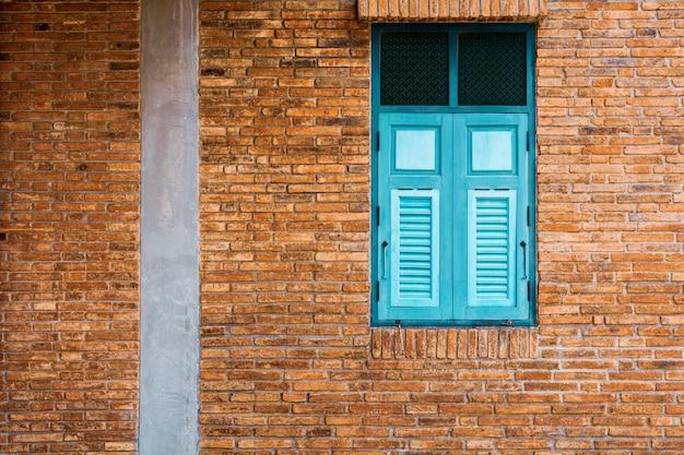 Janela de madeira verde e azul clássica no edifício de tijolo antigo.