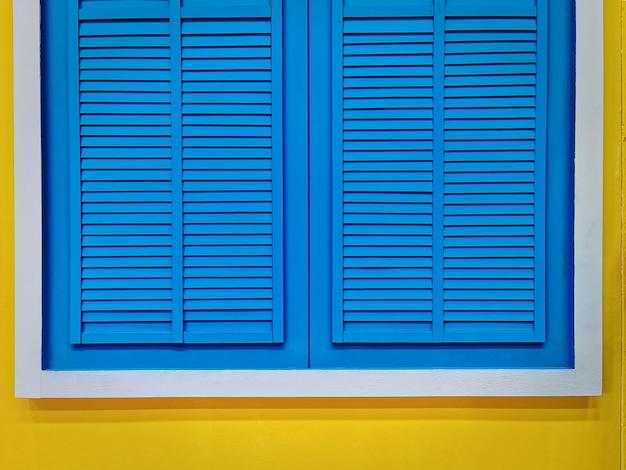 Janela de madeira vintage azul com moldura branca na parede amarela vívida