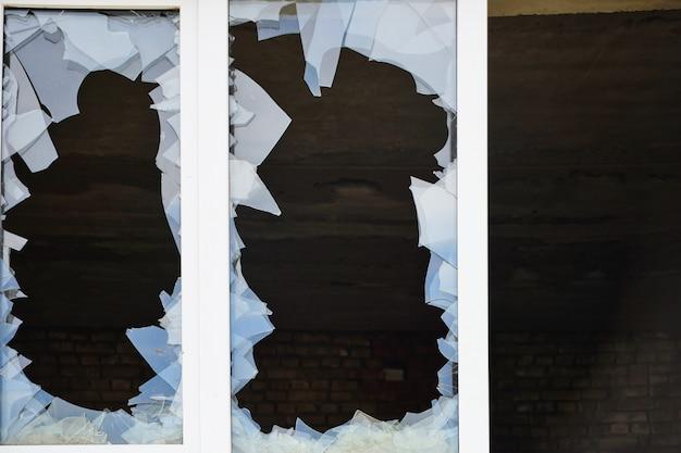 Janela de vidro quebrada do lado de fora, foto de close de um buraco em uma janela quebrada