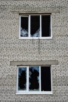 Janela de vidro quebrada perto da foto de um buraco em uma janela quebrada