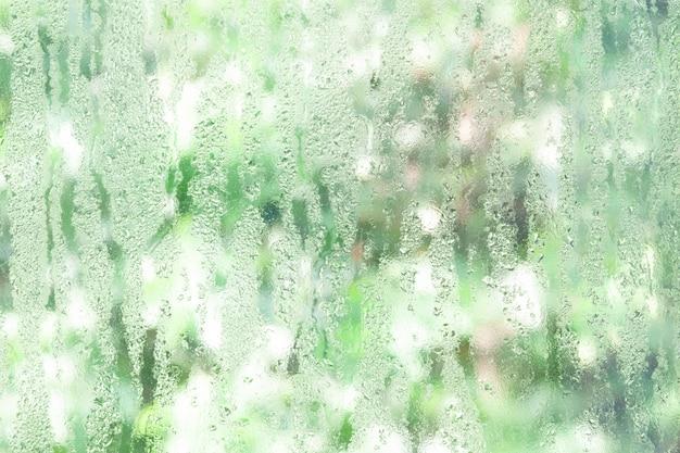 Janela de vidro transparente com gotas de água, natureza verde para o fundo