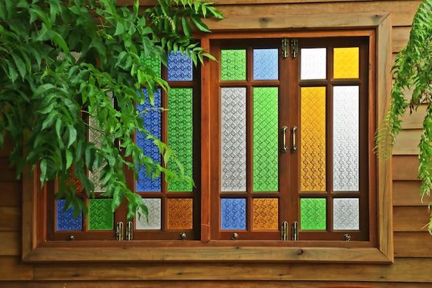 Janela de vitral, janela de madeira do estilo tailandês com folhas verdes.