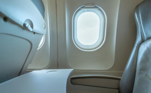 Janela do avião com luz solar branca. assento de couro do avião da classe econômica.