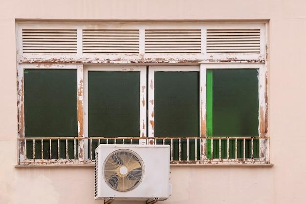 Janela em madeira pintada deteriorada devido às intempéries na fachada de um edifício no brasil