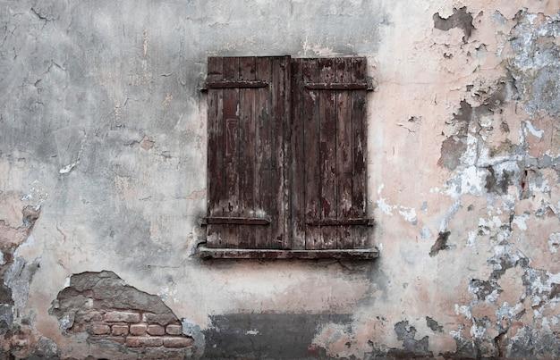 Janela fechada com venezianas de madeira velhas no fundo da parede descascada